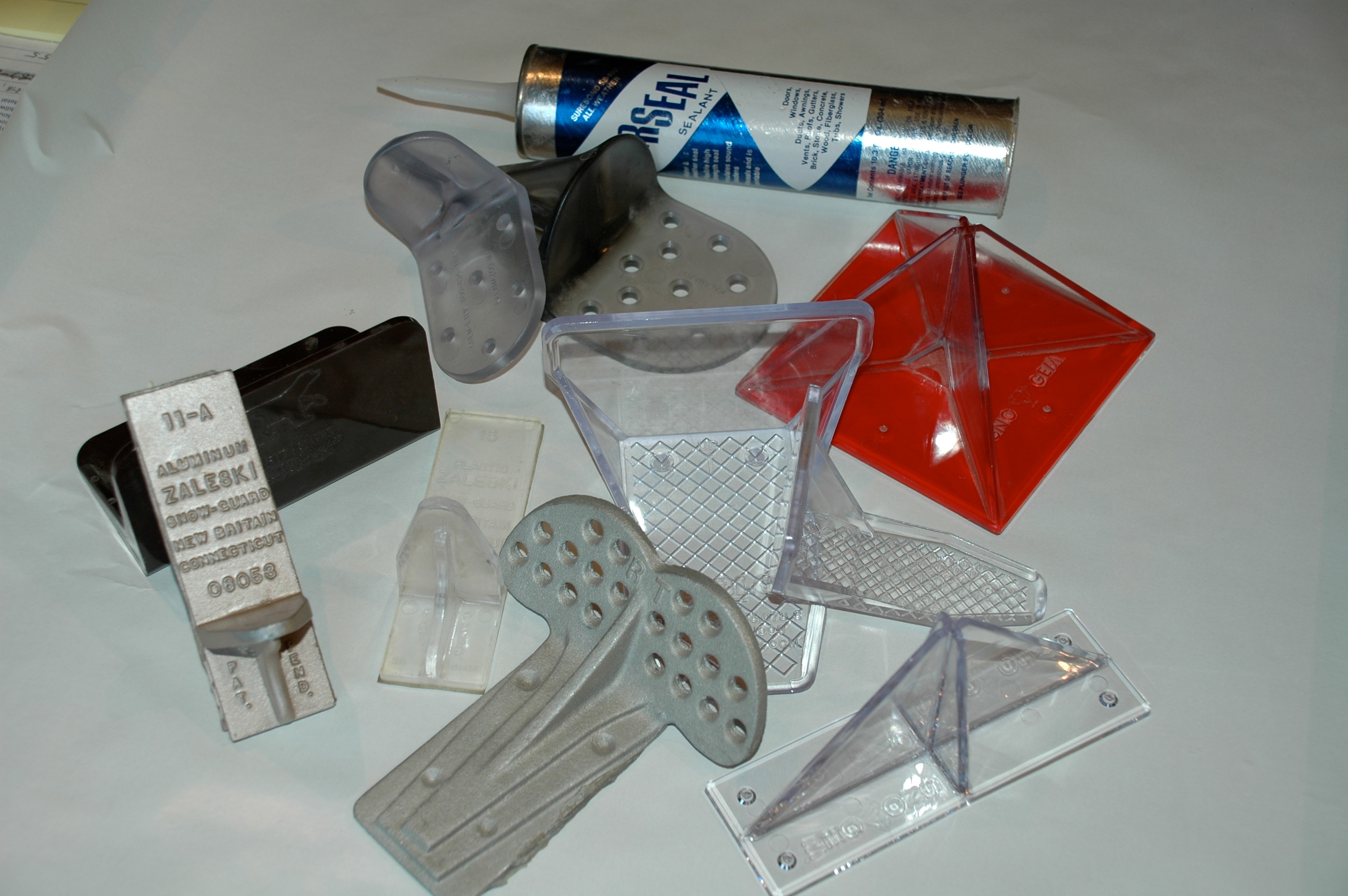 Glue-on snow guards and adhesive