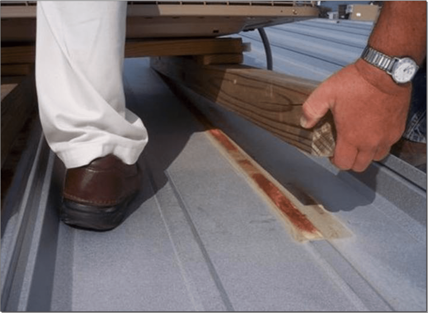S-5! Wrong way to install HVAC - Image shows how mounting with wood can encourage moisture to become trapped and induce corrosion shown on metal panel-min