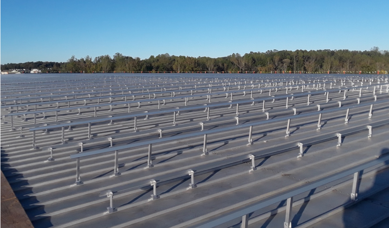 S-5!® - Rail-mounted solar panel installation on a commercial facility – using ≈ 9,000 standing seam clamps – no holes (penetrations) needed in metal roof